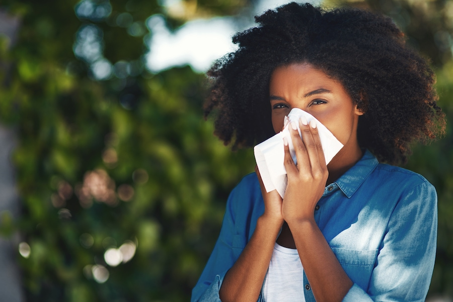 girl blowing nose outdoors due to not using her ac to help relieve allergy symptoms