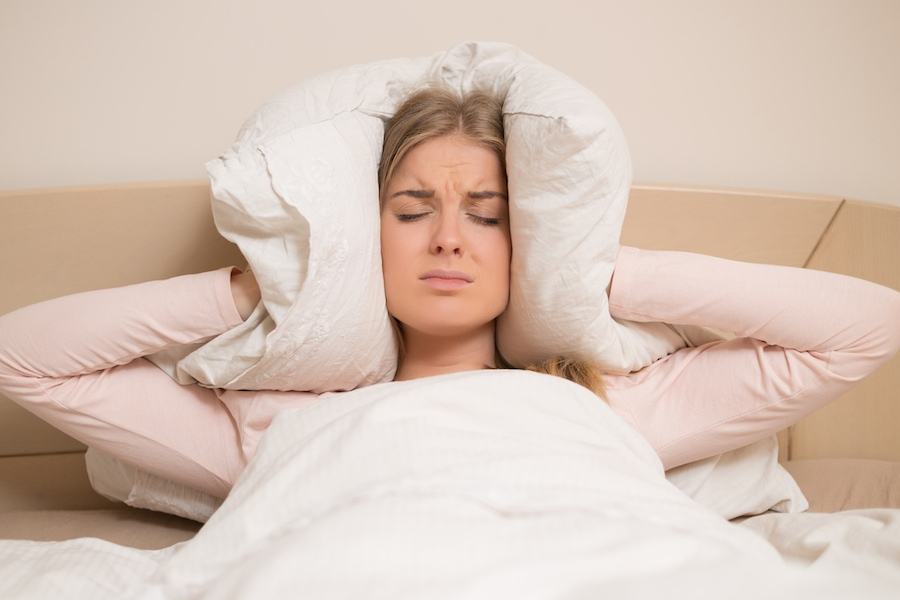 woman covering her ears due to loud air conditioner making noise