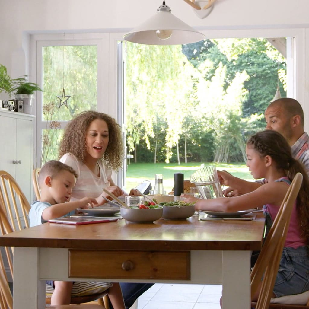 Happy family gathered around the table feeling healthy through having clean indoor air quality.