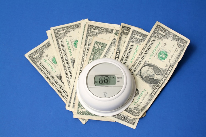 Money and thermostat showing how you can save money on your air conditioning and summer energy bill.