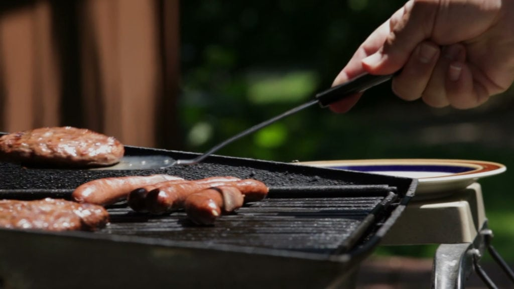 Man deciding to cook outside and following the energy saving tip.